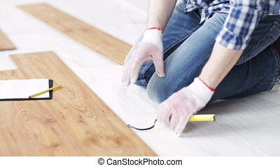 close up of man measuring flooring and writing - repair,...
