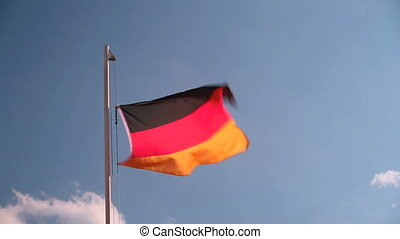 Hoisting a Germany flag in front of a blue sky