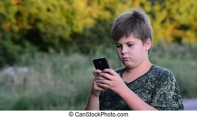 Teenage boy uses smartphone in the open air - Teenage boy...