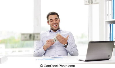 happy businessman with money and laptop in office -...