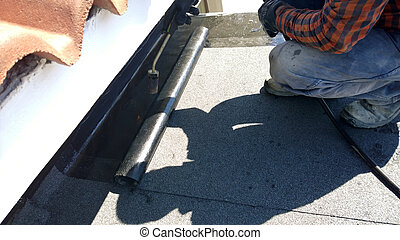 Roofer preparing part of bitumen roofing felt roll for...