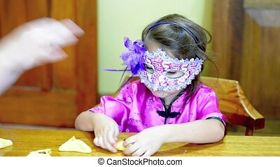 Jewish child preparing Hamantaschen cookie cooking in Purim...