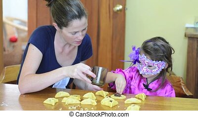 Jewish Mother and child preparing Hamantaschen cookie for...