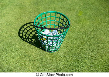A full bucket of golfballs on the driving range