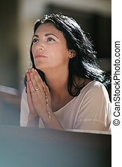 Woman praying - Beautiful woman with a rosary praying in the...