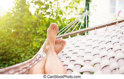 Man in a hammock on a summer day, close up photo
