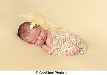 Sleeping Newborn Baby Girl Swaddled in Yellow - A portrait...