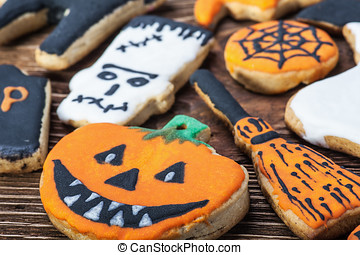 Handmade Halloween cookies on a wooden table focus on...