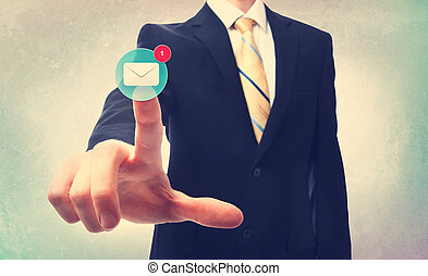Business man pressing an email button on a blurred background