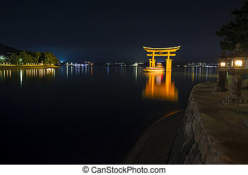 A ship passing under the famous orange shinto gate of...