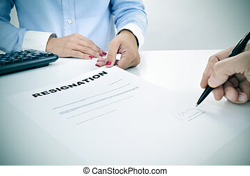 man signing a resignation document - closeup of the hand of...