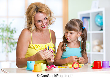 kid and mother play colorful clay toy in nursery - kid girl...