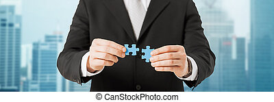 man trying to connect puzzle pieces over city - business,...