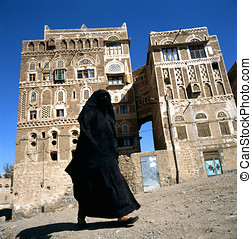 Muslim Woman in Burka walking in Sanaa, Yemen - A veiled...