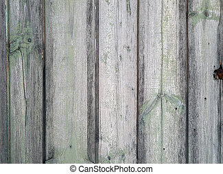 Fragment of an old wooden fence with the remains of green...