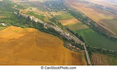Aerial View Of Yellow Harvest Field And Hilly Terrain -...