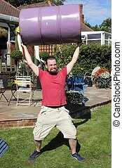 Strongman - A man lifting a 50 gallon drum above his head in...