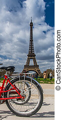 Rear red bicycle wheel over Eiffel tower on background in...