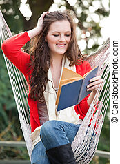 Teenager reading a book - A beautiful teenager sitting on a...