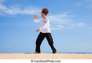 Tai chi in the dunes - young woman in black and white making...