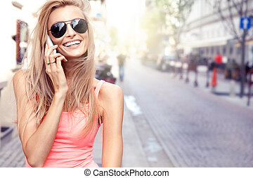 Happy blonde woman talking by mobile phone. - Beautiful...