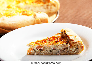 Quiche Lorraine - one slice in a plate, the other part in...