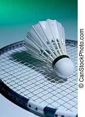 Badminton racket and shuttlecock on its strings (green...