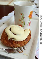 Cinnamon roll with a cup of coffee