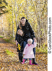 mother with her daughters in autumnal nature