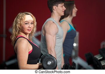 Group of people training with freeweights in fitness center...