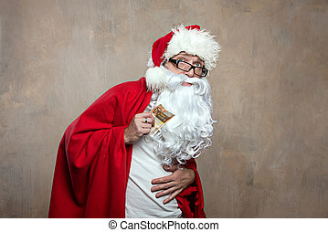 Sick old Santa in home clothes keeps a banknote and holds...