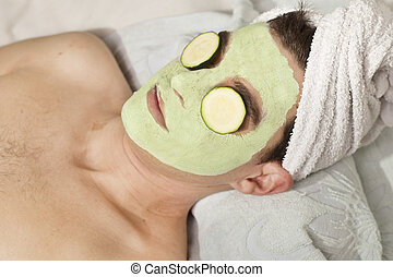 man with clay facial mask in beauty spa