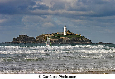 A windsurfer sails past Godrevy lighthouse West Cornwall - A...