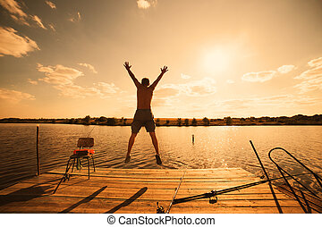 Happy man jumping on pier with lake and sky in background, sunset warm light
