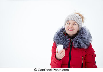 Happy smiling female in red winter jacket holding mobile phone, outdoors against the snow