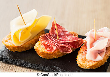 Antipasto food with cheese, salami, and tork ham with...