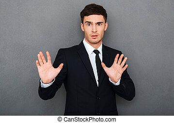 Stop it Frustrated young man in formalwear keeping arms...
