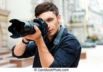 Ready to shoot. Confident young man photographing something...