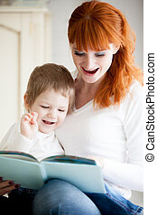 Mom reading her son book - Education. Red-haired young...