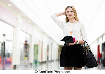 Pensive young woman out of money after shopping time -...