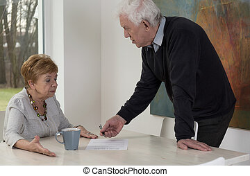 Signing a document - Man is persuading woman to sign a...