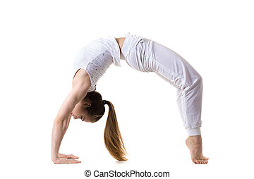 Wheel yoga Pose - Young fitness model in white sportswear...