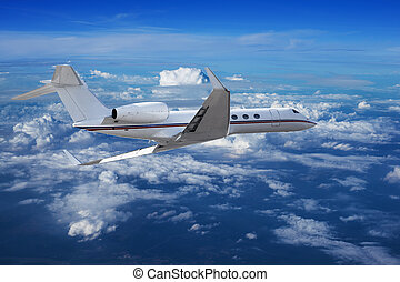 Private jet cruising above the clouds