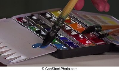Brush taking watercolor in palette - The brush come wet and...
