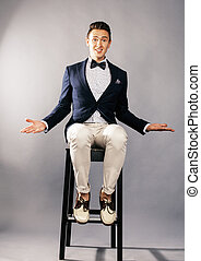 young handsoman businessman fooling aroung with chair in...