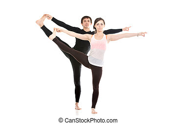 Extended Hand-To-Big-Toe yoga pose with partner - Two sporty...