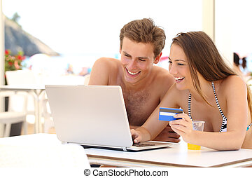 Couple buying online on holidays with a laptop and credit...