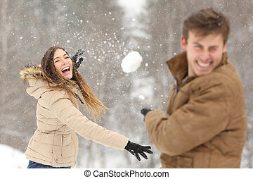 Couple playing with snow and girlfriend throwing a ball in...