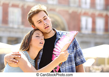 Couple suffering summer heat and fanning with a fan