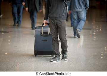 Man with suitcase - Young man with suitcase walking in...